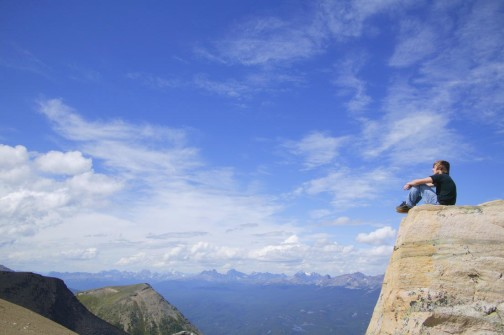 Boy on top of mountain enjoying the view